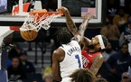 New Orleans Pelicans forward Brandon Ingram (14) dunks in front of Minnesota Timberwolves forward Anthony Edwards (1) in the second half of an NBA bas