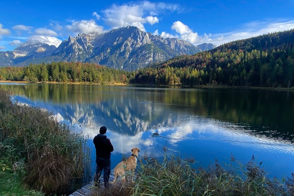 A man and his dog watch the Alps mountains at a lake near Mittenwald, Germany, Friday, Oct. 26, 2021. (AP Photo/Matthias Schrader)