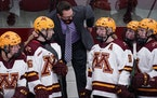 Brad Frost, middle, has a 418-87-35 career record as Gophers women's hockey coach.
