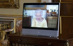 Queen Elizabeth II appears on a screen via videolink from Windsor Castle, where she is in residence, during a virtual audience at Buckingham Palace, L