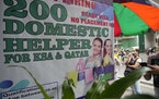 A woman stands beside a sign about hiring domestic helpers for the Mideast outside an office in Manila, Philippines on Thursday, Oct. 21, 2021.