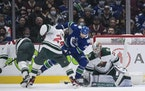 The Canucks' Tanner Pearson (70) and the Wild's Matt Dumba (24) vied for the puck in front of Wild goalie Cam Talbot during the first period Tuesd