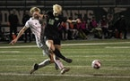 Stillwater Area Jacob Ralston (14) collides midair with Mounds View forward Sam Hoyt (12) as Hoyt kicks the ball in the second half. Mounds View playe