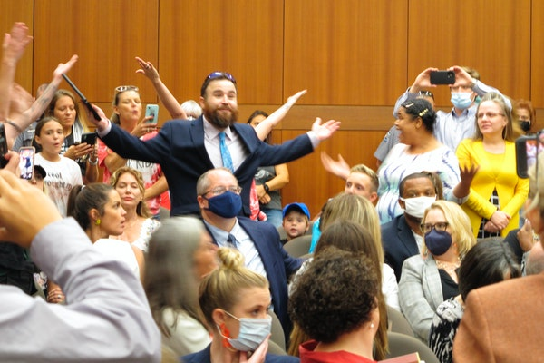 A crowd of angry, largely unmasked people objecting to Louisiana Gov. John Bel Edwards' mask mandate for schools shouts in opposition to wearing a f
