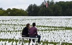 People sit among white flags near the Washington Monument in Washington on Sept. 17, 2021, that are part of artist Suzanne Brennan Firstenberg's tem