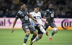 Vancouver Whitecaps' Brian White takes a shot on goal as Minnesota United's Michael Boxall defends