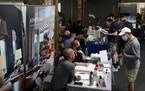 In this Sept. 22, 2021, file photo, prospective employers and job seekers interact during a job fair in the West Hollywood section of Los Angeles. The