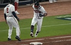 Atlanta Braves' Eddie Rosario runs past Atlanta Braves first base coach Eric Young Sr. after hitting a three run home run during the fourth inning in